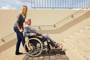 Junge Frau schiebt ältere Rollstuhlfahrerin Treppen hoch